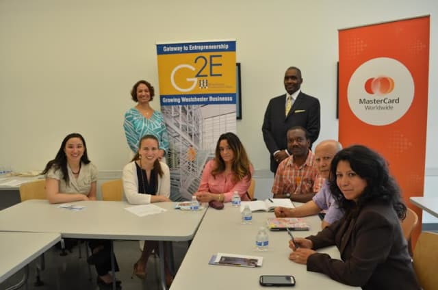 Eridania Camacho, director, Gateway to Entrepreneurship and WCC professor Scorpio Rodgers, (standing), are joined by MasterCard's Elizabeth Liu, program manager, and Monica Chaves, senior program officer, Global Partnership, left.