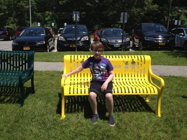 """Hastings' Ben Johnson sits on the """"Buddy Bench"""" he helped bring to his Hillside School campus."""