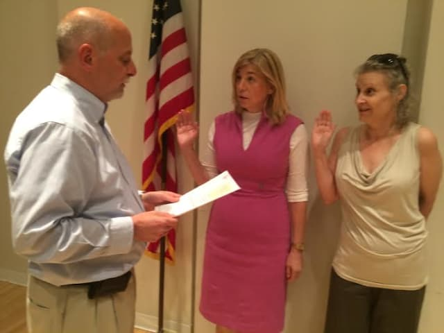 Greg Varian swears in, from left, Haina Just-Michael (president) and Emery Schweig (vice president) to the board of trustees at the New Rochelle Public Library for terms ending in 2019.