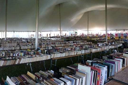 Thousands of books are stacked underneath a giant tent on Jesup Green before the Westport Library's annual Summer Book Sale in a past year. The event begins Saturday.