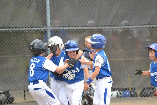 Matt Claps is congratulated by teammates after hitting a grand slam for the Norwalk Cal Ripken 9-year-old All-Stars in a game against South Meriden.