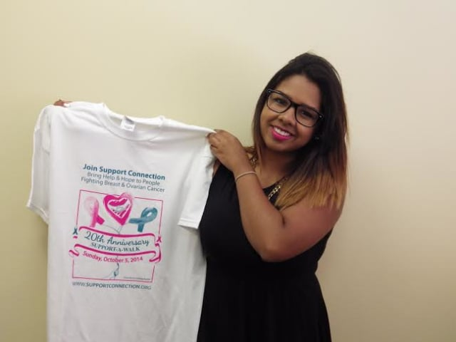 Lindsey Torres of Peekskill, NY, holding the Support-A-Walk tee-shirt that features her winning design.