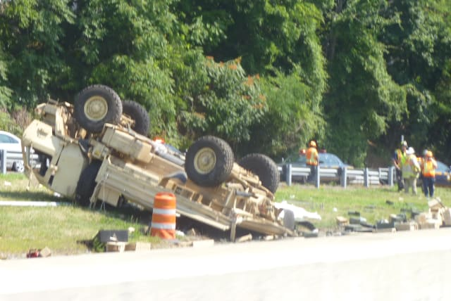 A Connecticut Army National Guard light medium tactical vehicle overturned on I-95 after collided with a sedan Thursday, Aug. 7.