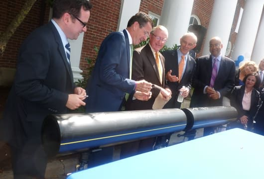 Gov. Dannel P. Malloy, second from left, jokes with Wilton First Selectman Bill Brennan, center, after they and other officials signed an 8-inch polyethylene pipe during a press conference Monday announcing the expansion of Yankee Gas into the town.