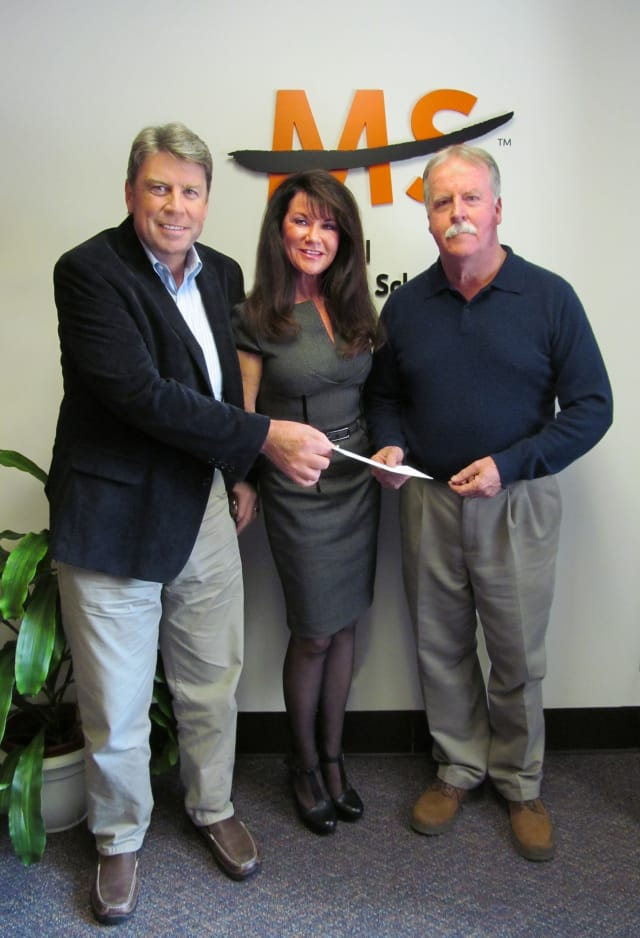 Greg 'Jake' Jacobson, left, and Mike Reilly, Ridgefield, present a check for $21,700 to Lisa Gerrol, president and chief executive officer of the National MS Society, Connecticut Chapter.