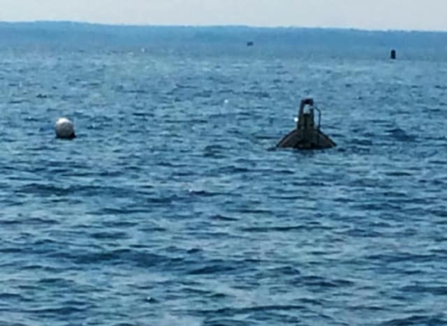 The bow of a sunken 26-foot Bayliner sticks out of the water in Long Island Sound. It sunk Saturday night west of Captain Island but all five people were rescued by Greenwich Police.