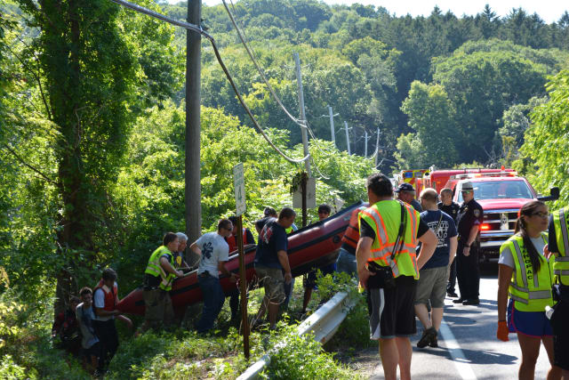 A boat is carried by responders near the Croton Falls Reservoir in Carmel.