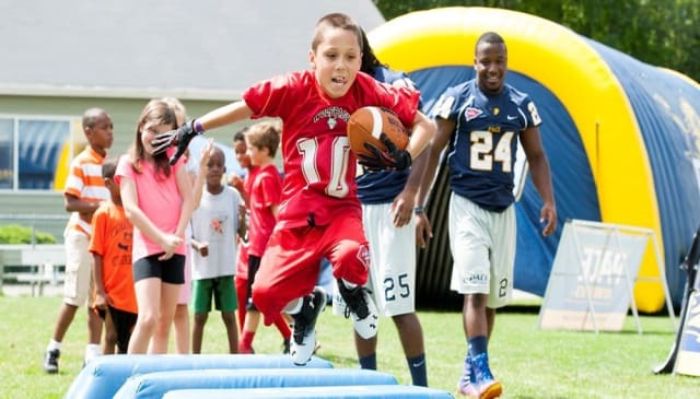 Pace University football players coordinated youth clinics for children at fan fest in Pleasantville.