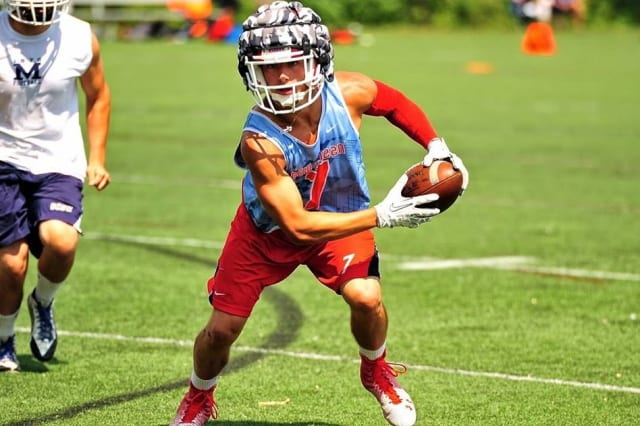 A New Canaan football player runs with the ball during a summer tournament.