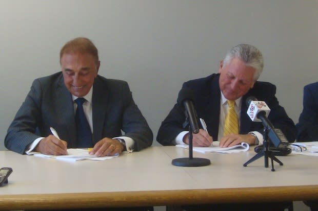 Michael DiScala and Norwalk Mayor Harry Rilling sign agreements to develop the property on Smith Street Thursday.