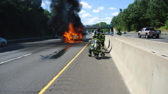 Firefighters battle a blaze on I-95 in Norwalk on Thursday.