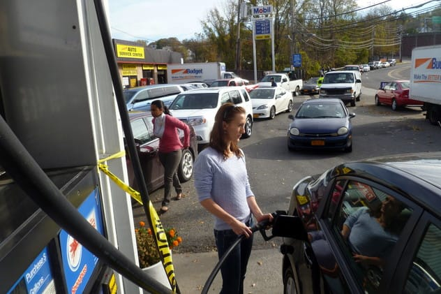 Katarina Kandracove fills her car at a Mobil station on Yonkers Avenue Thursday as a line of cars waits behind her. The city has announced it will now ration gas and limit customers to 10 gallons per visit.