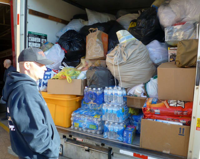 Yonkers firefighter Tim Sullivan stands in front of a U-Haul truck packed with donations bound for Hurricane Sandy victims in Queens.