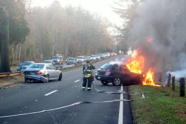 A Westport firefighter puts out flames in one of the two cars involved in an accident Wednesday morning on the Merritt Parkway. Both drivers said they hit a coyote that had wandered onto the road.