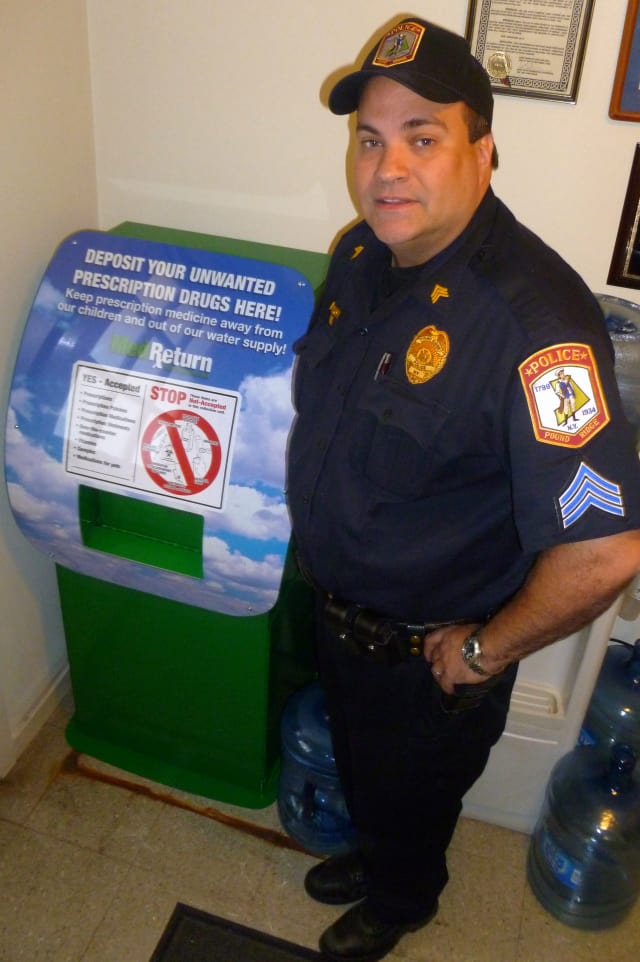 Pound Ridge police Sgt. Tom Mulcahy will oversee the prescription drug disposal program. Here he stands next to the disposal receptacle in the police station lobby.