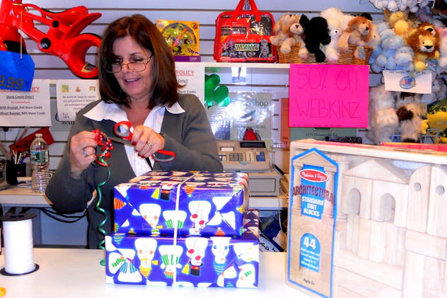 Denise Edwards of Briarcliff Toy Shop wrapping a holiday present last year. On Saturday, small retailers are offering discounts for Small Business Saturday.
