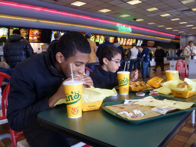Yonkers' Ricardo Fortuna and his brother, Omar, enjoy a meal at Nathan's Famous Hot Dogs Sunday, the final day the restaurant was open.