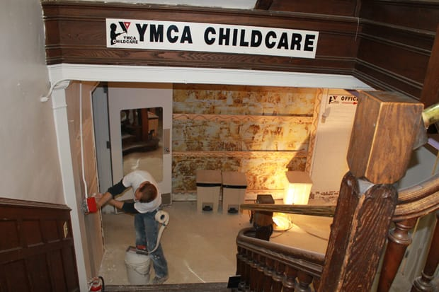 A worker repairs a flood-damaged wall in the Westport Weston Family Y's Child Care Center on Thursday.