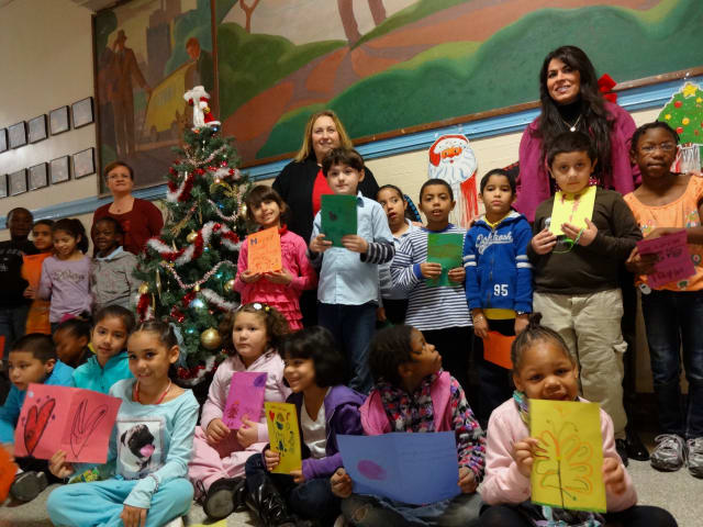 Yonkers School 23 Principal Christine Montero (right) and Asst. Principal Theresa Abate (let) joined second-grade teacher Amy Wells and her students as they made holiday cards for U.S. troops throughout the U.S. and abroad.