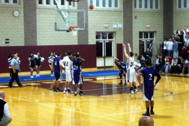 The Scarsdale High School boys basketball team, in white, started its season with a 50-23 win against Lincoln.