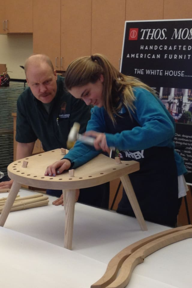 A Whitby School eighth-grader helps handcraft a rocker, under the guidance of Thos. Moser's master furniture maker Warren Shaw.