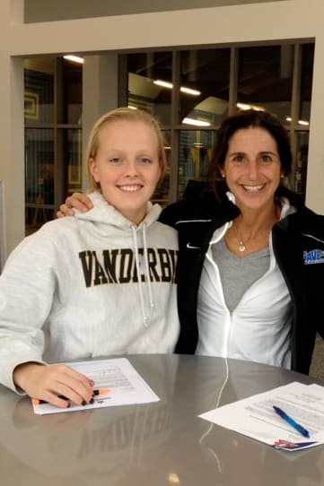 Darien swimmer Olivia Leunis, left, signs her letter of intent to attend Vanderbilt with coach Marj Trifone.