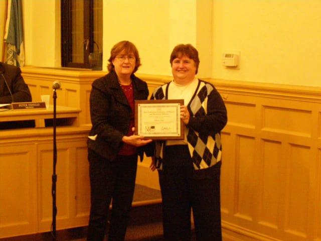 Mayor Anne H. McAndrews presents Eileen Finn, village clerk, with the NYCOM Service Award
