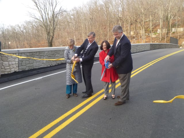 State Transportation Commissioner James Redeker, second from left, cuts the ribbon officially reopening Redding's Simpaug Turnpike Bridge.