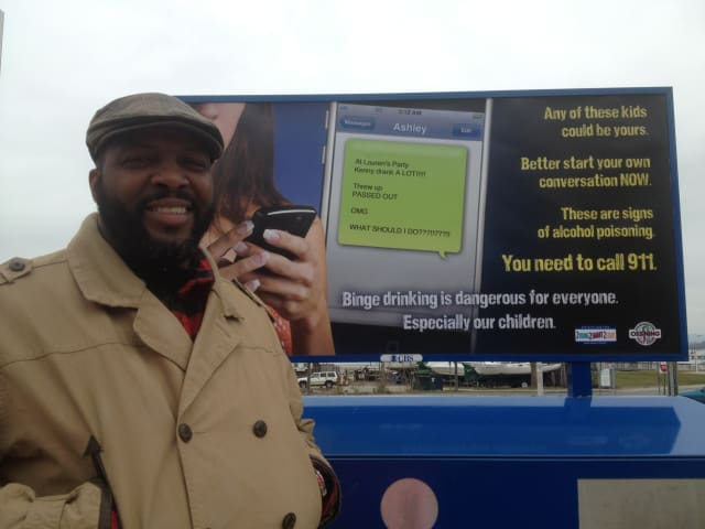 Ossining Police Detective Ed Walker at the train station in front of an ad warning parents of the dangers of underage drinking.