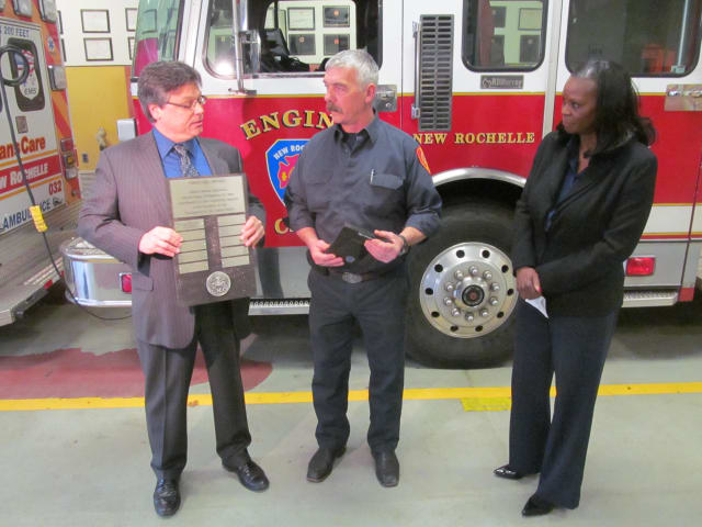 New Rochelle firefighter Byron Gray is awarded Liberty Mutual's Firemark award at the city's station three firehouse Thursday.