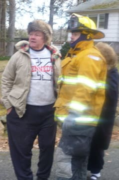 School Board Trustee Dr. Peter Treyz talks to a firefighter as he watches his South Salem home burn.