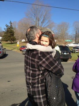 A parents and child reuniting Friday morning after a school shooting in Newtown, Conn.