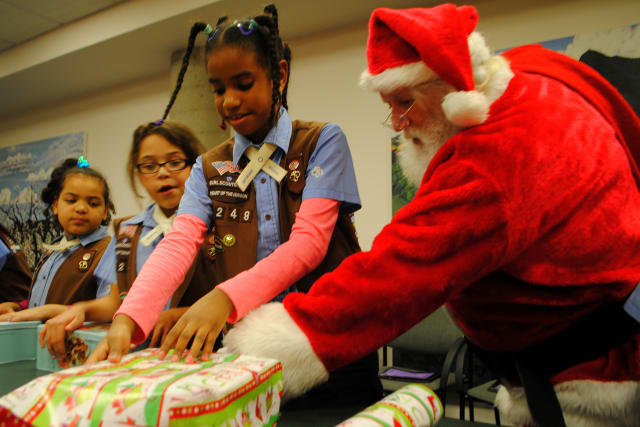 "Santa helps a Girl Scout wrap a present, at Hudson Valley Hospital Center's ""Santa's Helpers"" event."