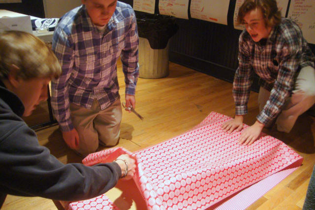 Darien teens team up to wrap a large box at the Depot's annual Wrap Up event, which is running through Sunday.