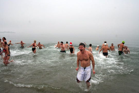 Participants in a past year's Team Mossman Polar Plunge at Westport's Compo Beach brave the icy waters of Long Island Sound for charity.
