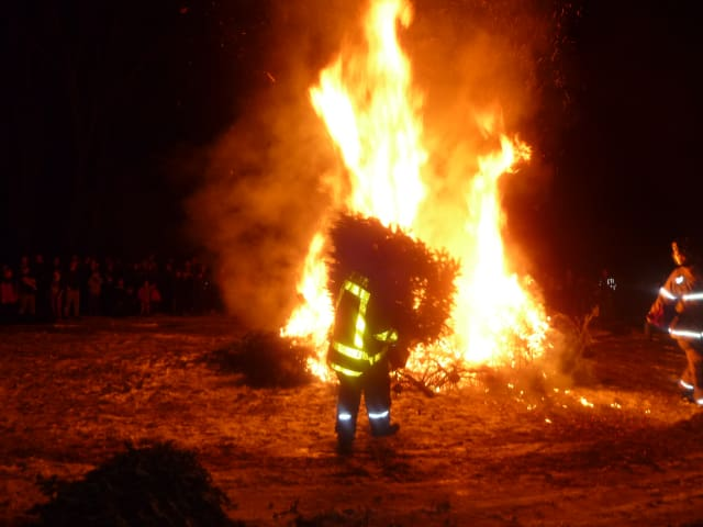 A firefighter feeds a tree into the bonfire with Weston residents watching.