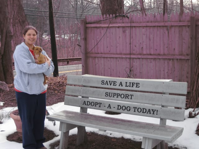 Adopt-A-Dog Inc. kennel manager Kristen Alouisa stands with a puppy named Cinnamon outside of the shelter, which is at 23 Cox Ave., Armonk.