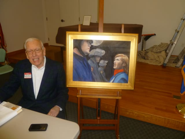 Keith Brooks, who leads Occupy Weston, sits in front of Occupy 2, an original oil painting.