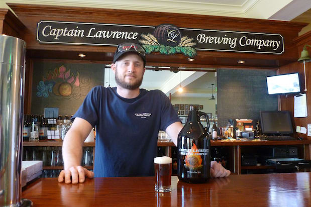 "Ryan Kipp, a brewer at Captain Lawrence Brewing Company, stands with a sample of his new beer called ""The Pride of Elmsford."""