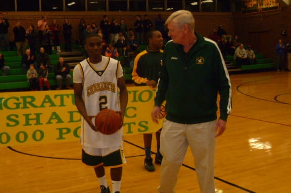 Trinity Catholic's Schadrac Casimir, left, receives a ball for scoring his 1,000th-career point from Mike Walsh before Friday's game against Danbury.