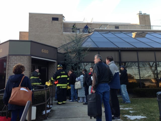 Residents of 680 W. Boston Post Road wait to gather belongings as firefighters ensure their safety upon re-entering the building.