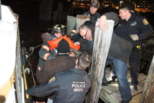 Emergency responders help a pilot and his passenger onto dock after their plane crashed into the Hudson River in Yonkers.
