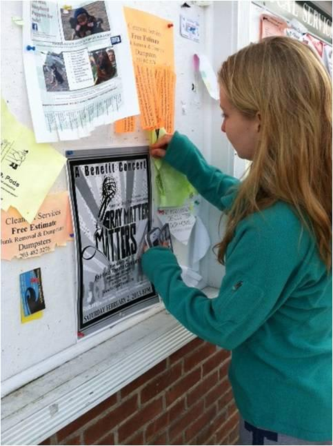 Clare Murray hangs a poster at Peter's Market in Weston to promote the benefit concert she planned.