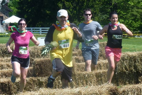 Runners make their way over hay bales during the Pineapple Race With Obstacles last May in Greenwich.