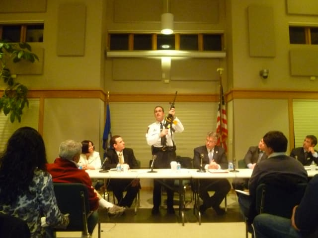 Redding Police Chief Douglas Fuchs shows off an assault rifle at a public forum on gun violence Monday night.