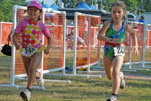 Norwalk's Cameron Stewart, right, races with Laura Pippitt of Rhode Island in the Mini Mossman Kids Triathlon last July.