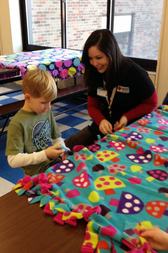 Red Cross Youth Services Associate Carissa Duro works on a comfort kit with a Primrose School student.