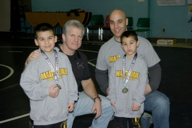 Norwalk Mad Bull wrestlers Jason (left) and Nicky Singer (right) attended last week's state tournament with coach Art Schad (second from left) and their dad, Jason.
