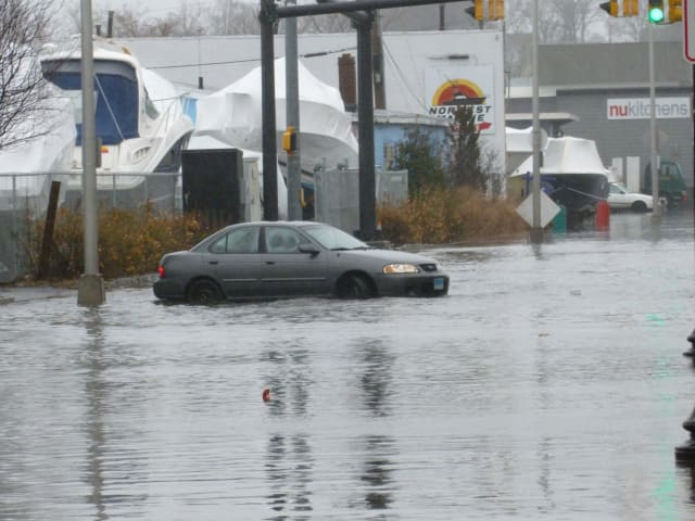 A car tries to drive through flooded Water Street in South Norwalk Wednesday following heavy rains that soaked the area.
