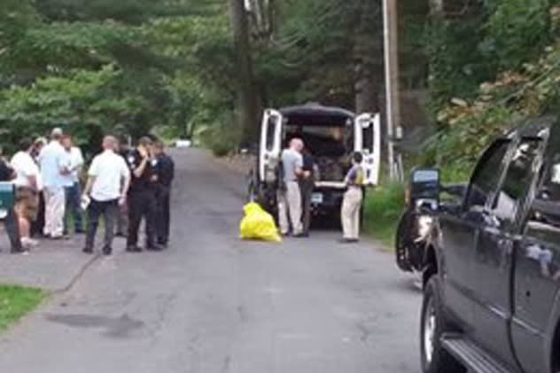 Local, state and federal officials investigate the delivery of a white powder to a Darien home Monday.